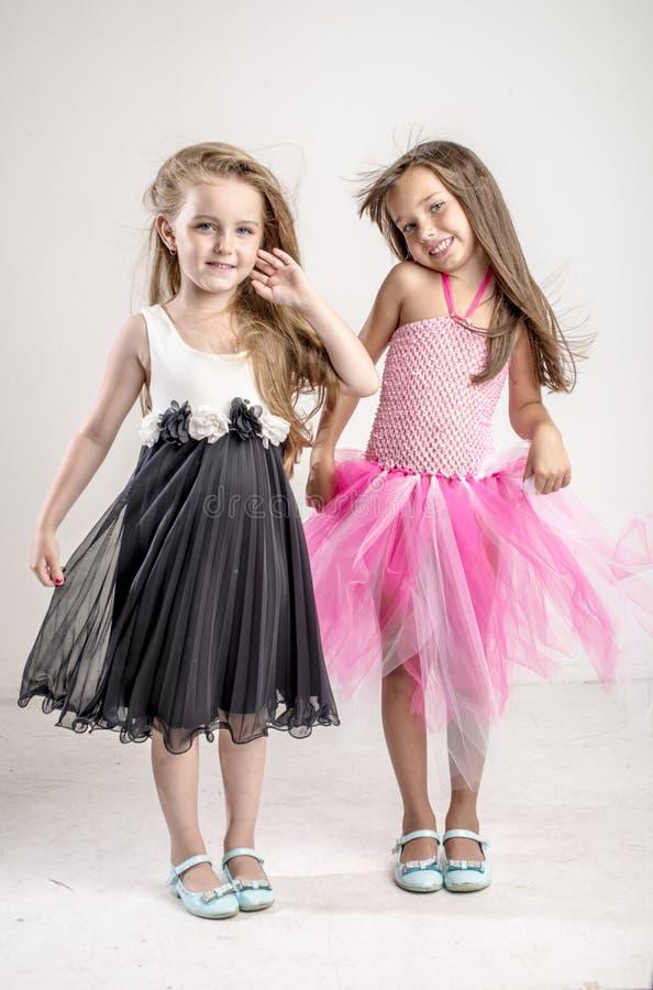 Zwei junge Mädchen sitzen im festlichen Gesang ihrer Schwester stockfoto