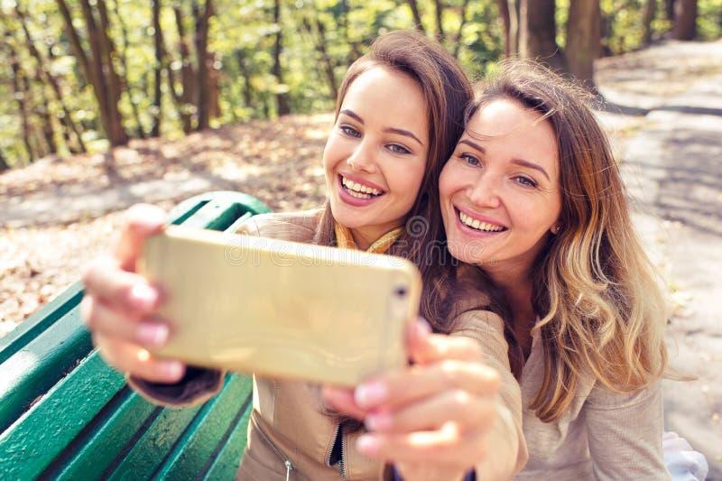 Zwei junge Mädchen, welche die Fotos machen selfie machen lizenzfreie stockfotografie
