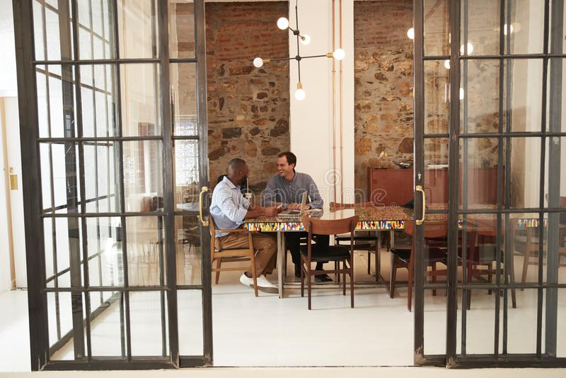 Zwei junge Männer bei einer Sitzung in einem Sitzungssaal stockfotografie