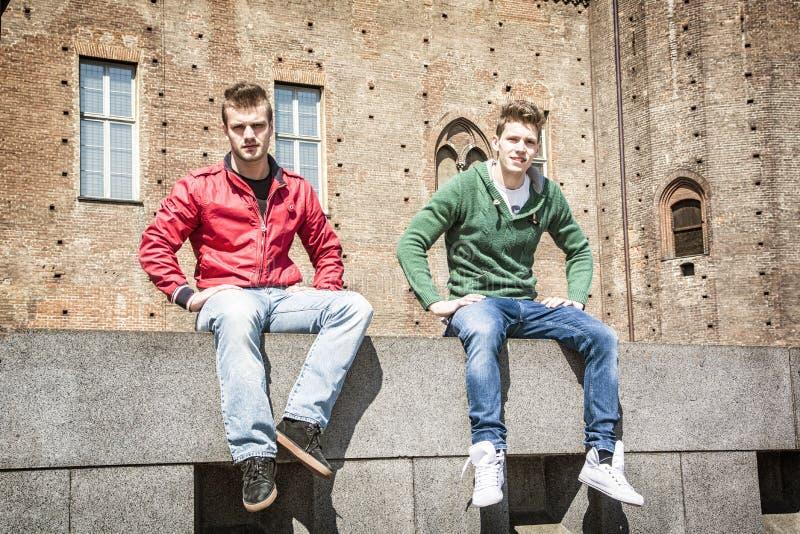 Zwei junge Männer, die auf niedriger Mauer in der städtischen Landschaft sitzen stockfotos
