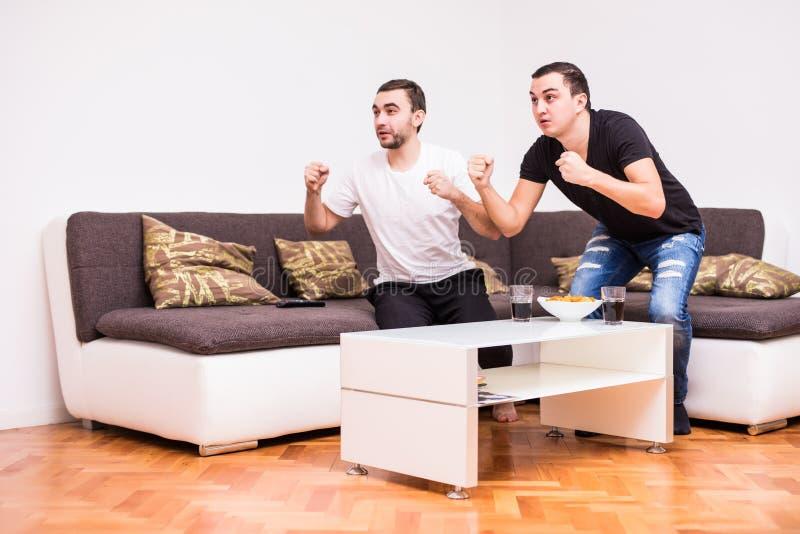 Zwei junge Männer, die eine Fußbalabgleichung auf Fernsehapparat überwachen Die junge Energie bemannt lizenzfreies stockfoto