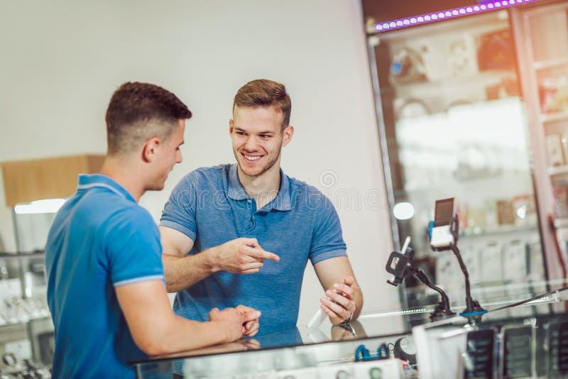 Zwei junge Männer, die intelligentes Telefon im Speicher wählen stockbild