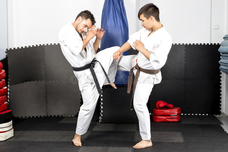 Zwei junge Männer in Kimono kämpfendem ashihara Karate-während ihres t stockbild