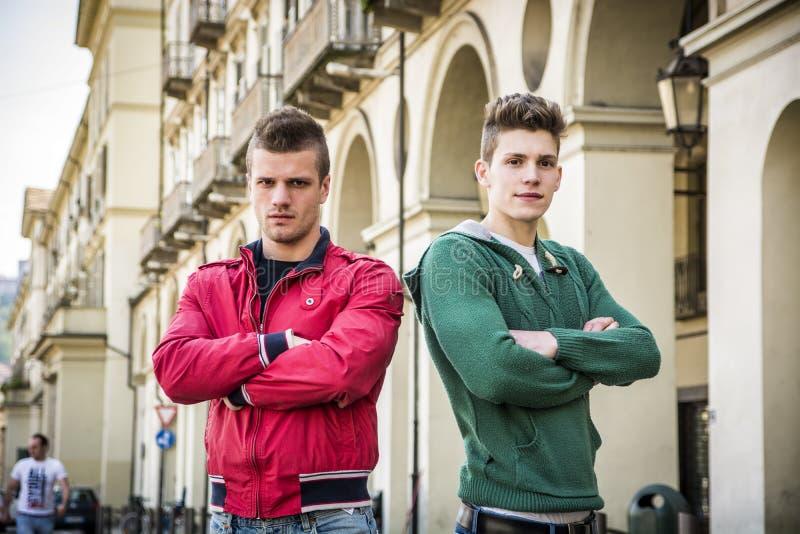 Zwei junge männliche Freunde, die im europäischen Stadtzentrum stehen lizenzfreie stockfotos
