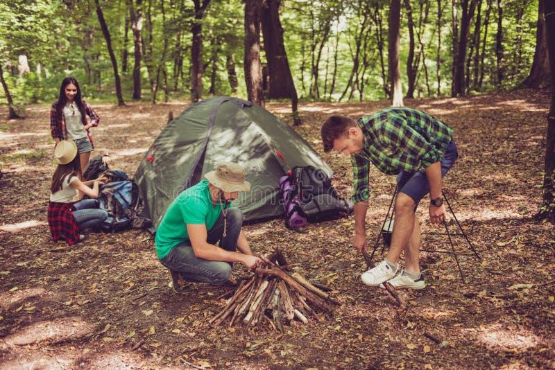 Zwei junge männliche Touristen im Holz, das Lagerfeuer FO organisierend lizenzfreie stockfotografie