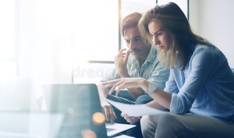 Zwei junge Mitarbeiter, die an Laptop-Computer im sonnigen Büro arbeiten Frau, die Papierdokumente verwahrt und auf Notizbuch zei stockfotografie