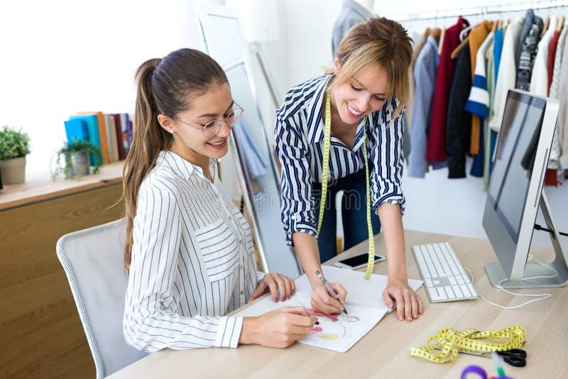 Zwei junge Modedesigner, die auf den Entwürfen der neuen Sammlung von Kleidung in der nähenden Werkstatt entscheiden lizenzfreie stockfotos