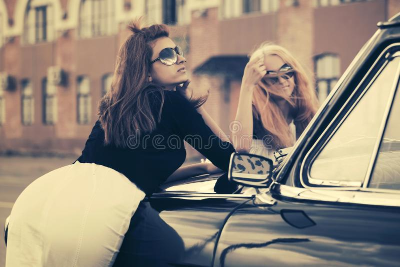 Zwei junge Modefrauen, die auf Weinleseauto auf Stadtstraße sich lehnen stockbilder