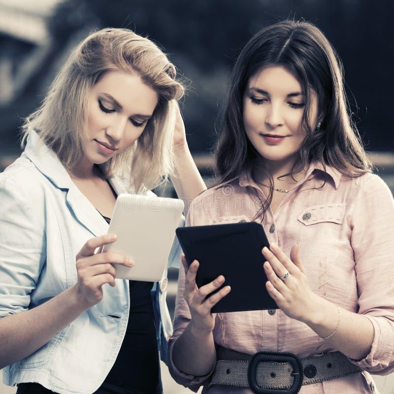 Zwei junge Modefrauen, die den Tablet-Computer im Freien verwenden stockfoto