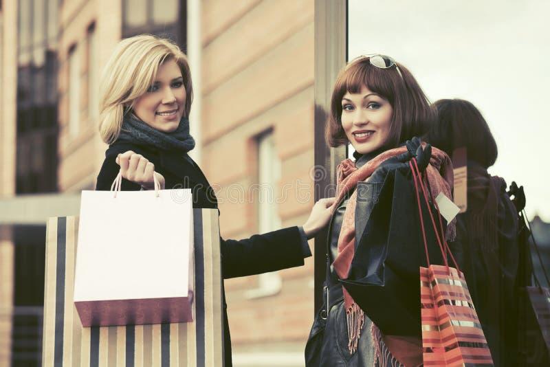 Zwei junge Modefrauen mit Einkaufstaschen nahe bei Malltür lizenzfreie stockfotografie