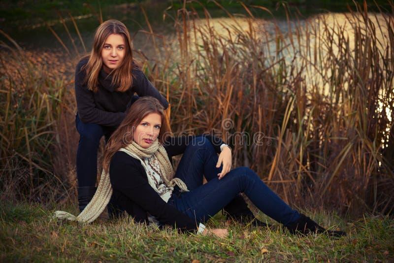 Zwei junge Modemädchen im schwarzen Pullover und dunkelblauen in den Jeans im Freien stockbild