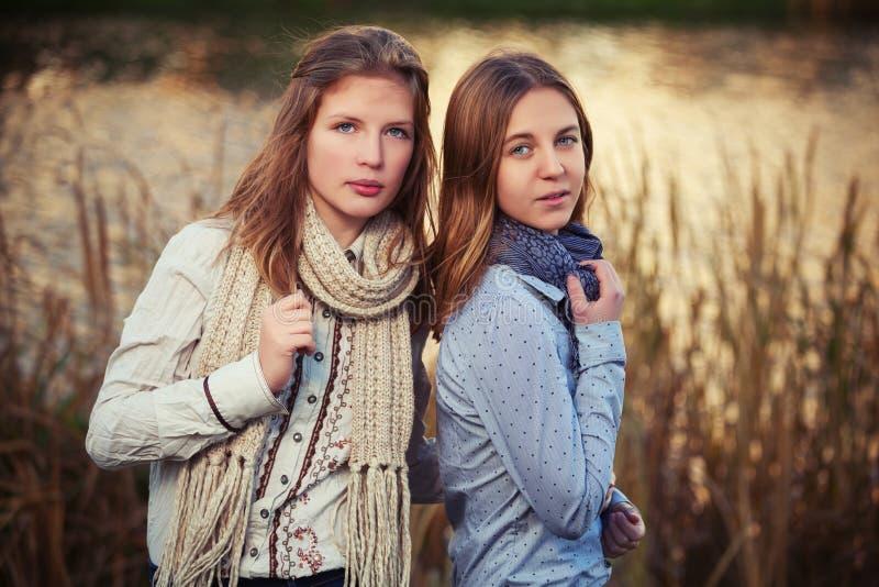 Zwei junge Modemädchen im weißen Hemd- und Schalgehen im Freien stockfotos