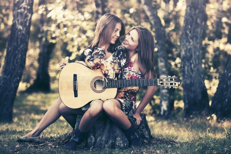 Zwei junge Modemädchen mit Gitarre im Sommerwald lizenzfreies stockfoto