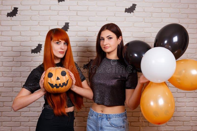 Zwei junge nette Frauen mit Kürbis und mehrfarbigem Ballone havi lizenzfreies stockfoto