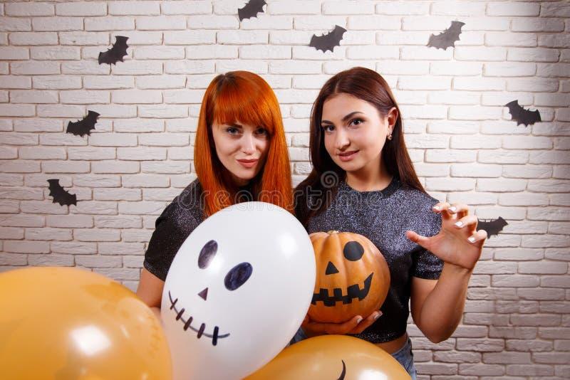Zwei junge nette Frauen mit Kürbis und mehrfarbigem Balloneisschrank lizenzfreies stockbild