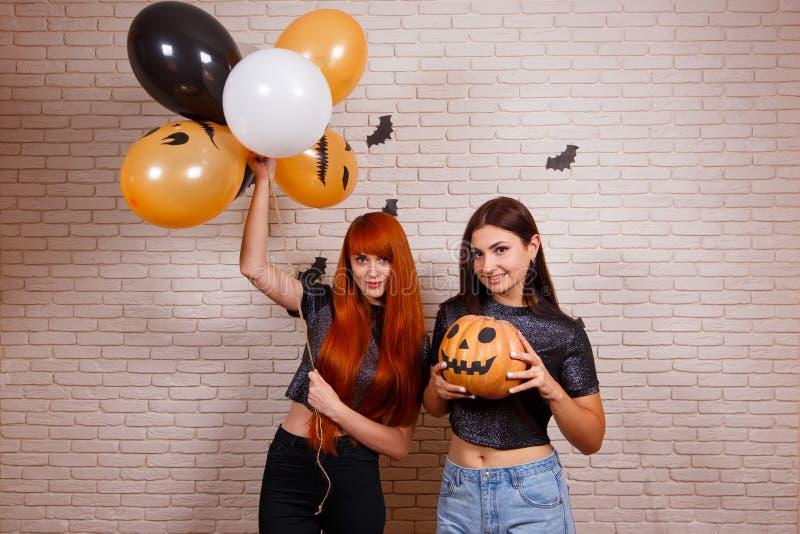 Zwei junge nette lächelnde Frauen mit Kürbis und gemalten Ballonen h stockfotos