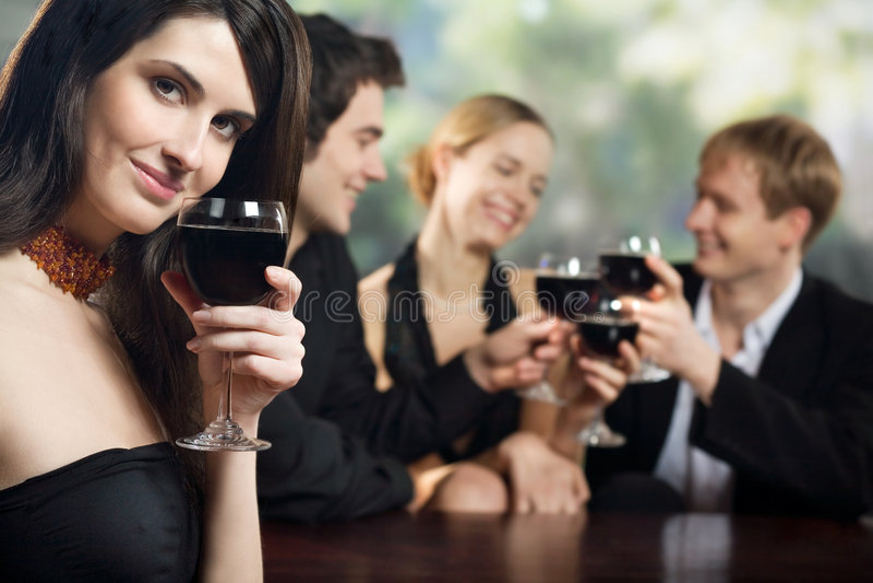 Zwei junge Paare mit Rotweingläsern an der Feier oder an der Party stockbild