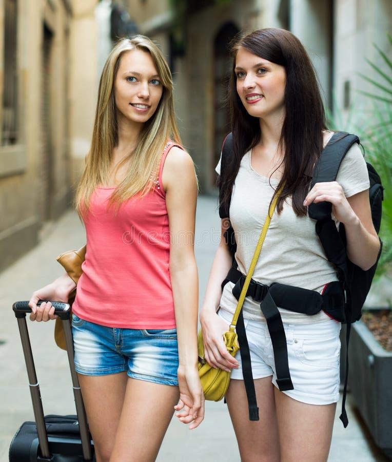 Zwei junge Reisende mit dem Gepäck, das zum Hotel vorangeht stockfotografie