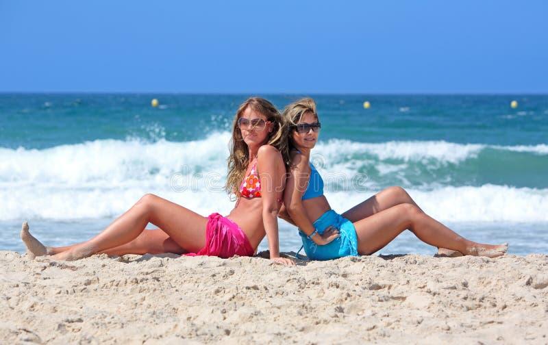 Zwei junge reizvolle und gesunde Mädchen, die auf einem sonnigen Strand sitzen lizenzfreies stockbild