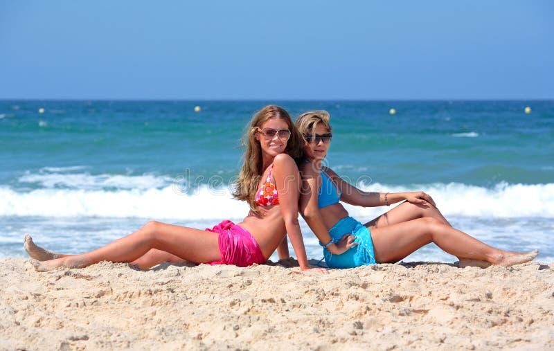 Zwei junge reizvolle und gesunde Mädchen, die auf einem sonnigen Strand sitzen stockfotos