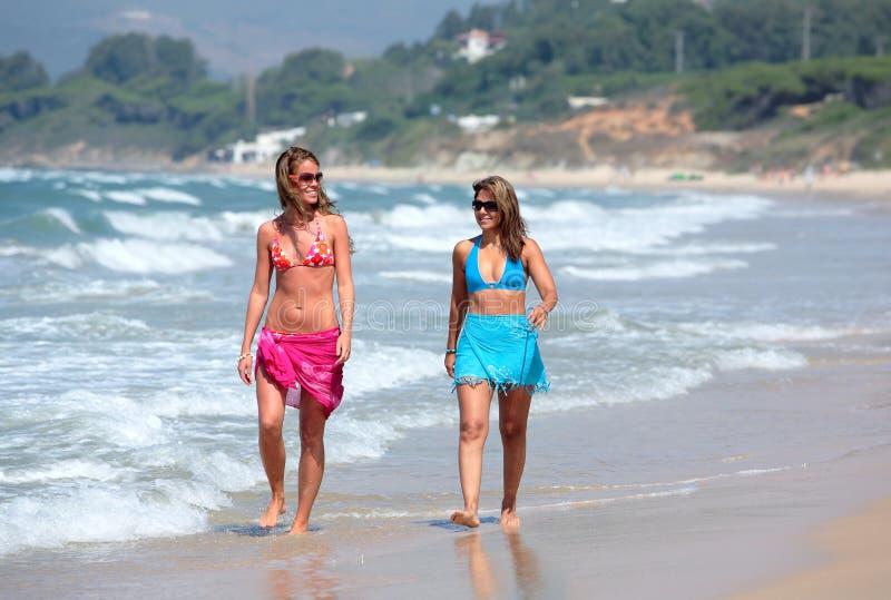 Zwei junge schöne gebräunte Frauen, die entlang sandigen Strand gehen stockbild