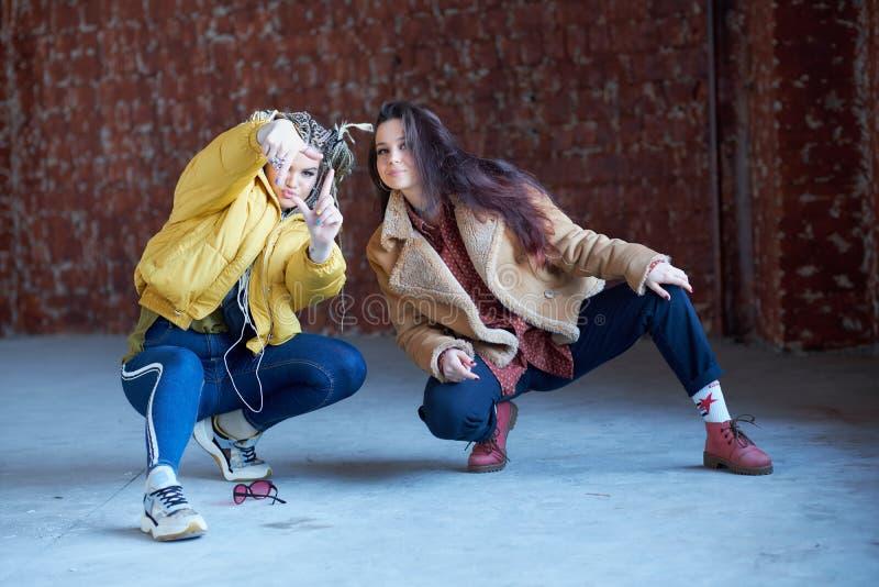 Zwei junge schöne lächelnde Hippie-Mädchen in der modischen Kleidung, die zusammen aufwirft junge sorglose Freunde lizenzfreie stockfotos