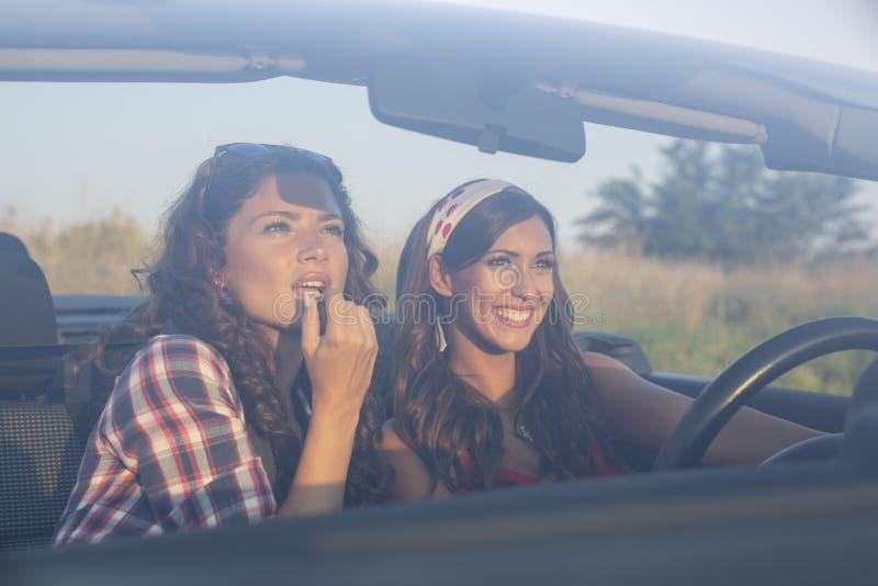Zwei junge schöne Mädchen, die auf Lippenstift in ein konvertierbares Auto fahren und sich setzen lizenzfreie stockfotos