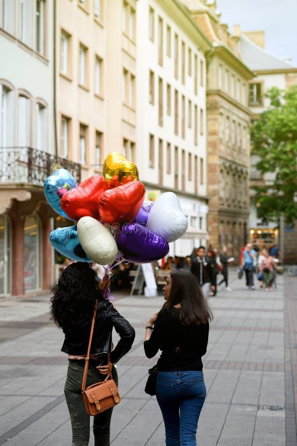 Zwei junge schöne Mädchen, die auf die Straße mit einem Heliumba gehen lizenzfreies stockbild
