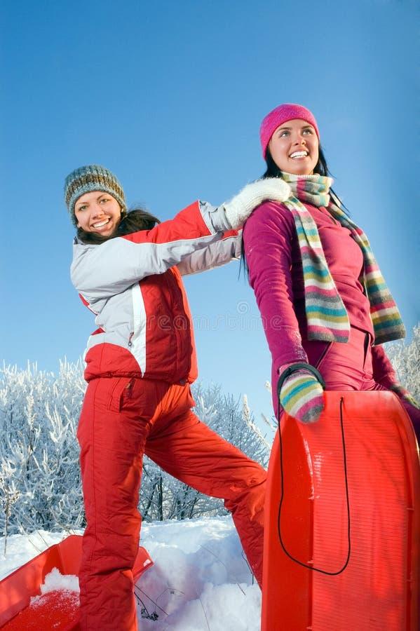 Zwei junge schöne Mädchen mit Schlitten lizenzfreie stockbilder