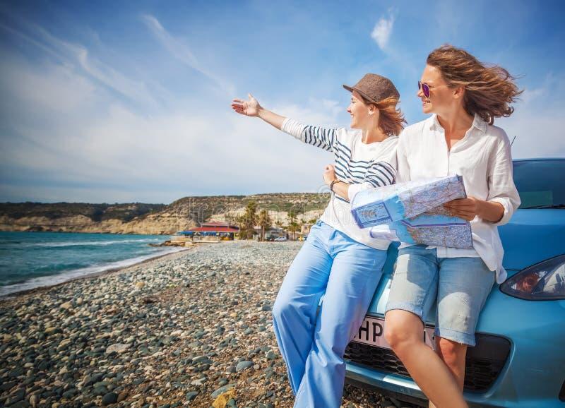 Zwei junge schöne Mädchenfreundinnen, die zusammen in einen Ca reisen lizenzfreie stockfotos
