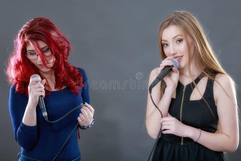 Zwei junge schöne singende Mädchen stockbilder