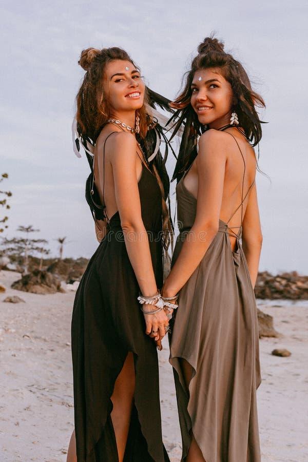 Zwei junge schöne stilvolle boho Mädchen auf dem Strand bei Sonnenuntergang lizenzfreie stockfotos
