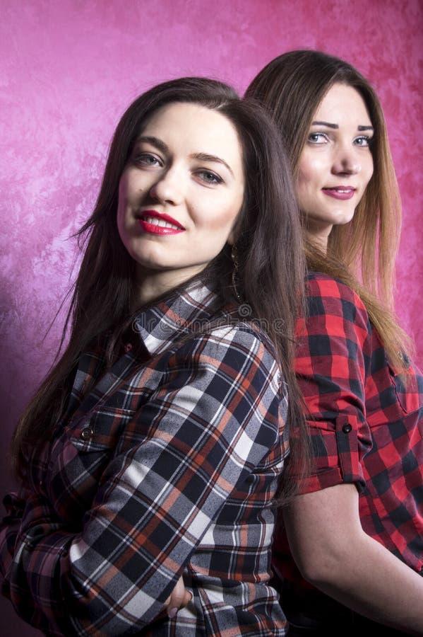 Zwei junge Schönheiten in den karierten Hemden stehen mit ihren Rückseiten miteinander stockfoto