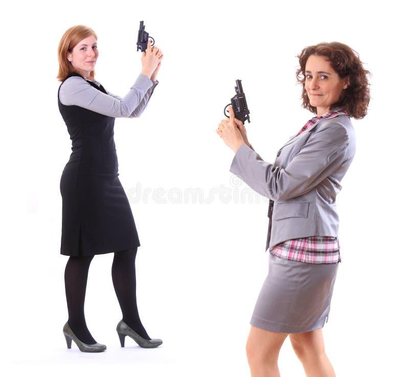 Zwei junge SchönheitsGeschäftsfrauen mit Gewehr lizenzfreie stockbilder