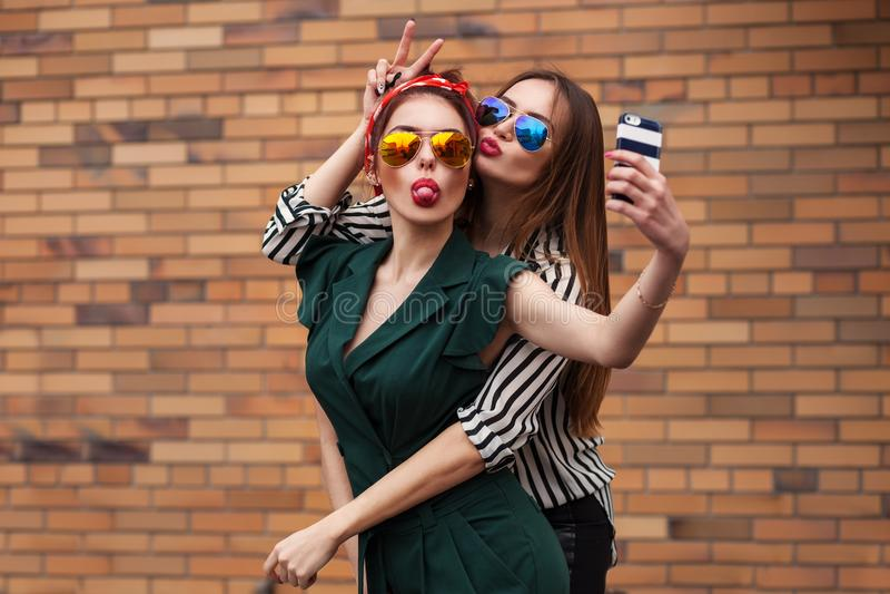 Zwei junge sexy Modefrauen, die für selfie aufwerfen und mit tonque lachen Lebensstilporträt auf Straßenstadthintergrund stockbild