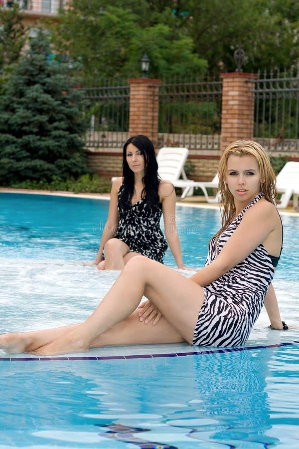 Zwei junge spielerische Freundinnen im Pool lizenzfreies stockbild