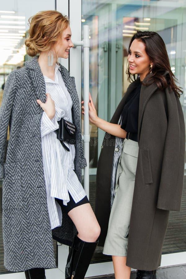 Zwei junge stilvolle Schönheiten, die nahe dem Speicher, sprechend stehen und lächeln, tragende Mäntel und haben Geldbeutel auf i lizenzfreie stockbilder