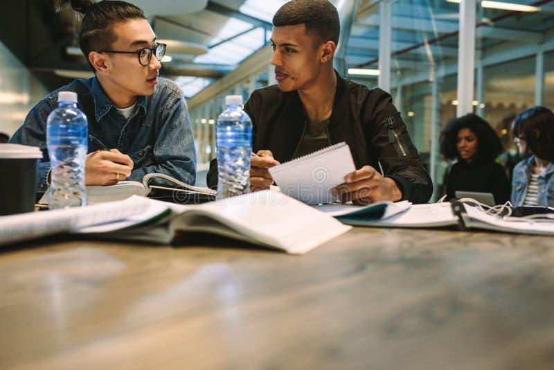 Zwei junge Studentenstudien zusammen auf einer Aufgabe Mitschüler, die zusammen an der Tablette mit Büchern und der Diskussion si lizenzfreies stockfoto