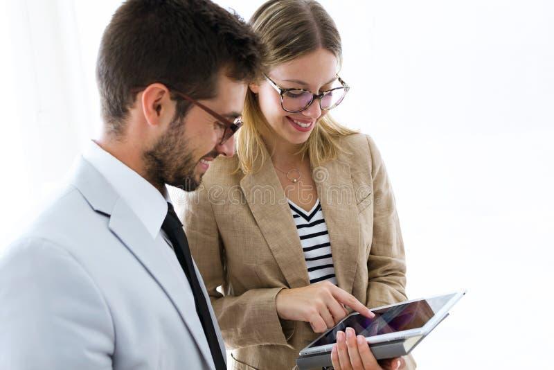 Zwei junge Teilhaber unter Verwendung der digitalen Tablette in einer Halle von ihnen Firma stockfotos