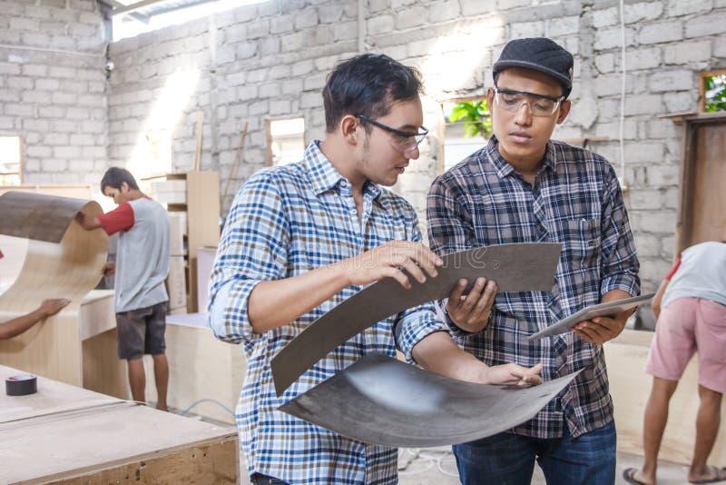 Zwei junge Tischler, die über Möbelmaterialien sich besprechen stockfotos