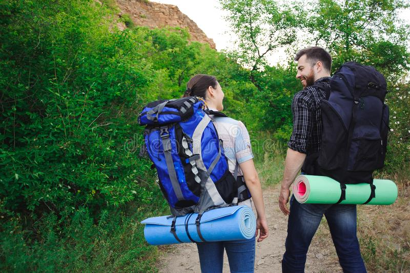 Zwei junge Touristen mit Rucksäcken Glückliche Freunde im Hintergrund des Grases und des blauen Himmels, entspannen sich Zeit am  stockbilder