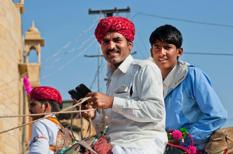 Zwei junge Viehhändler, die auf einem Kamel mit Handy sitzen stockfotos