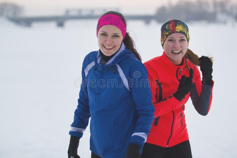 Zwei junge weibliche Athleten wirft auf dem Wintereisgebiet auf stockfoto