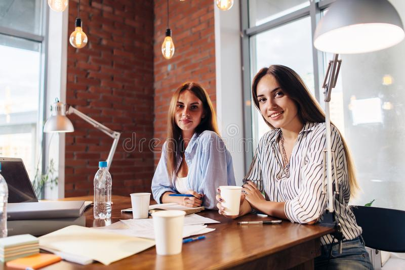 Zwei junge weibliche Unternehmer, die am Arbeitsschreibtisch während des Geschäftstreffens im modernen Konferenzsaal sitzen stockfotografie