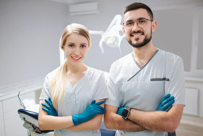 Zwei junge Zahnarztfachleute im Zahnheilkunderaum Sie werfen auf camer und Lächeln auf Leute halten Hände gekreuzt stockbilder