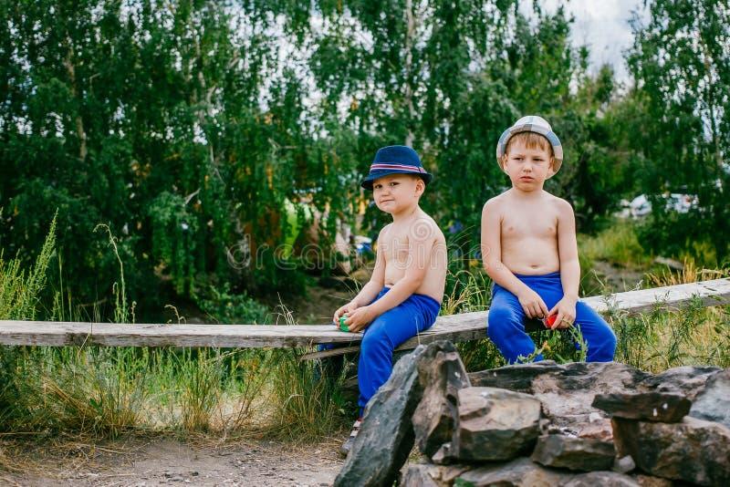 Zwei Jungen in den blauen Hosen und in den Hüten stockbilder