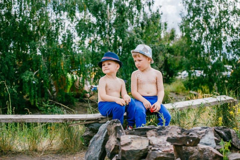 Zwei Jungen in den blauen Hosen und in den Hüten stockbild