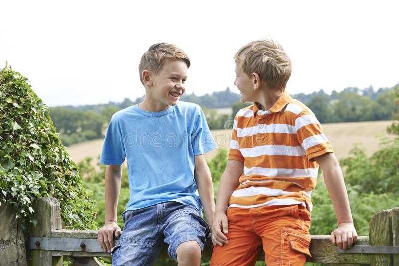 Zwei Jungen, die auf dem Tor zusammen plaudert sitzen lizenzfreies stockfoto
