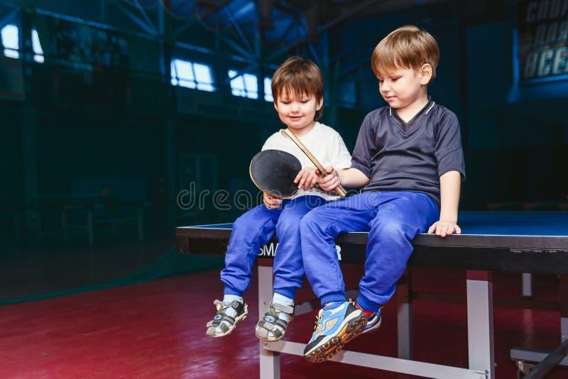 Zwei Jungen, die auf der Tennistabelle sitzen stockfoto