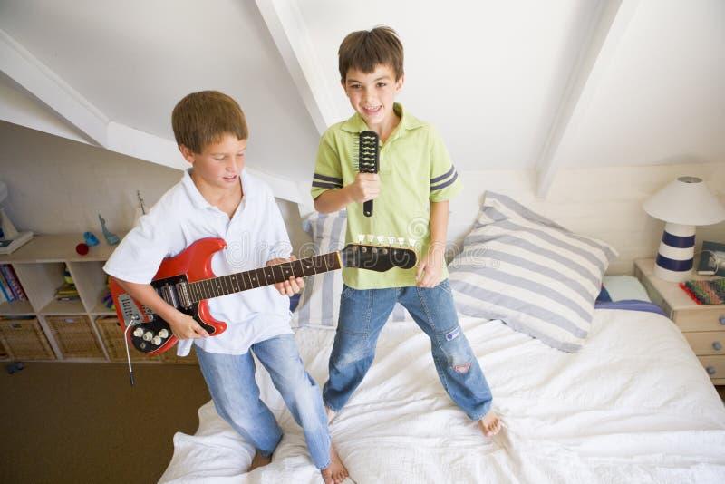 Zwei Jungen, die auf einem Bett-Spielen stehen stockfotos